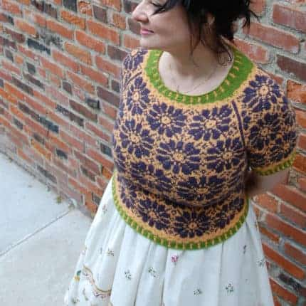 An orange sweater with a purple daisy pattern and a green accent at the neckline.