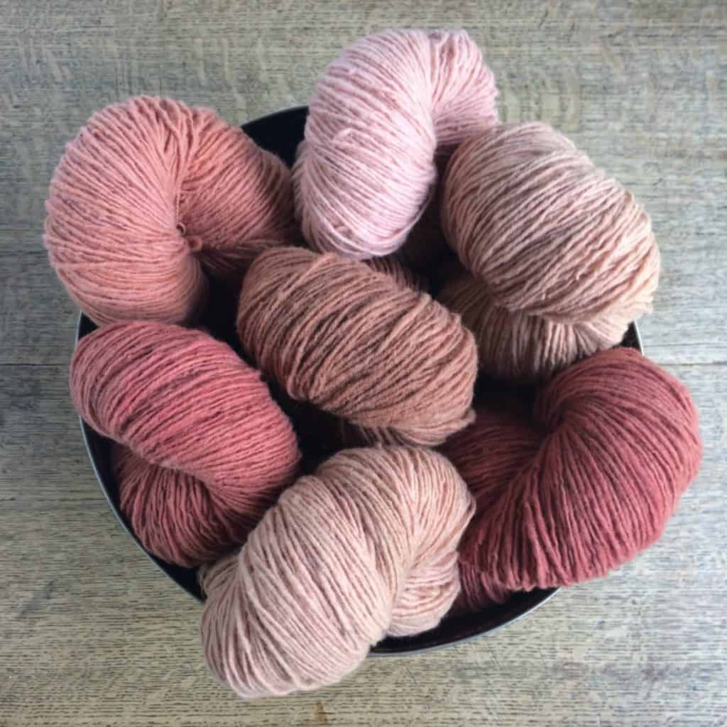Skeins of various shades of naturally-dyed pink yarn