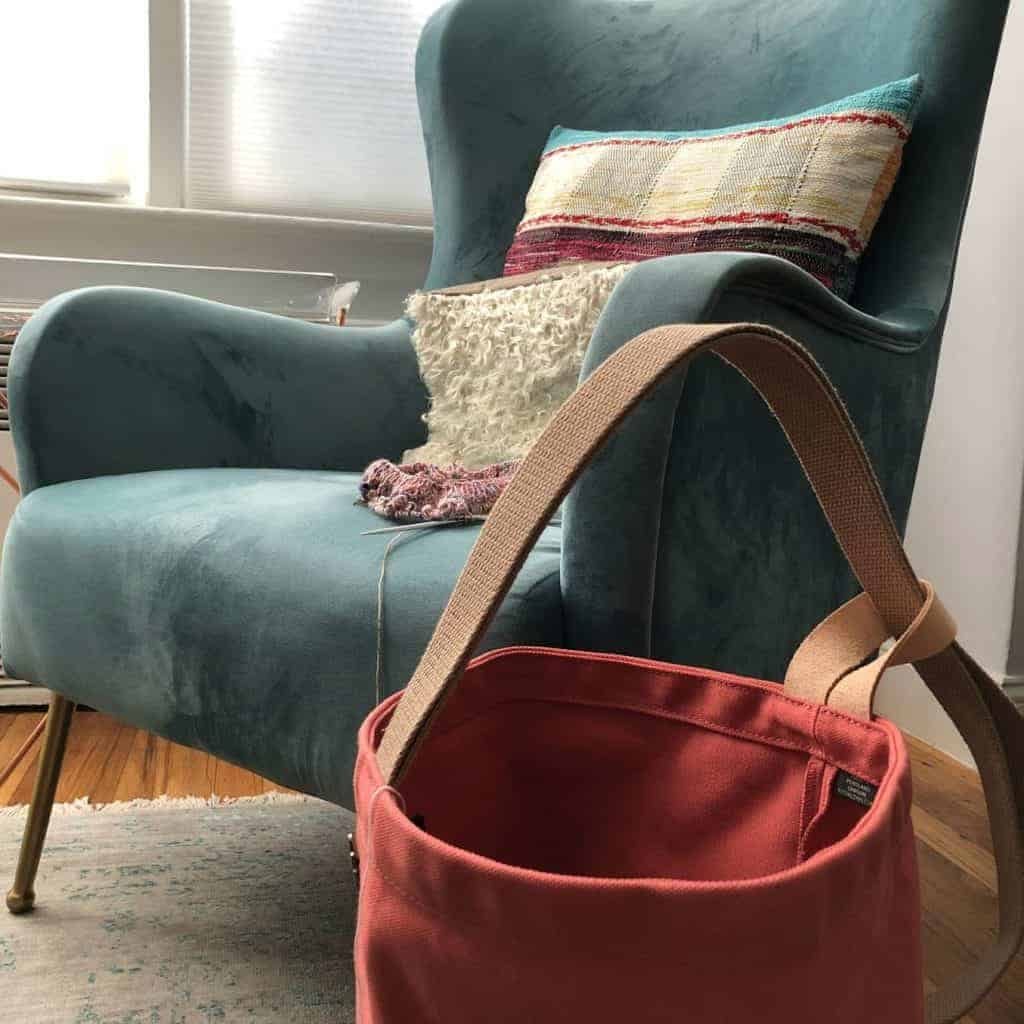 A salmon colored bag next to an aqua wing chair.