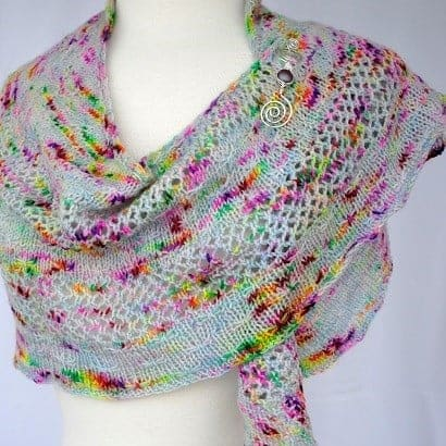 A speckled lace shawl with a silver shawl pin