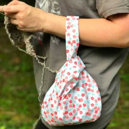 A project bag slung over a knitter's arm