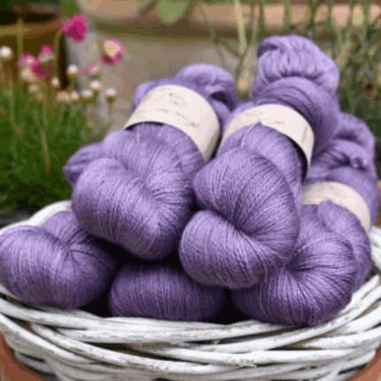 A white basket of purple yarn.