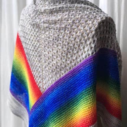 A lacy ivory shawl with a rainbow at the bottom