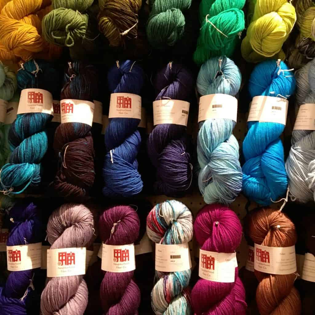 A wall of Neighborhood Fiber Co. hand-dyed yarn