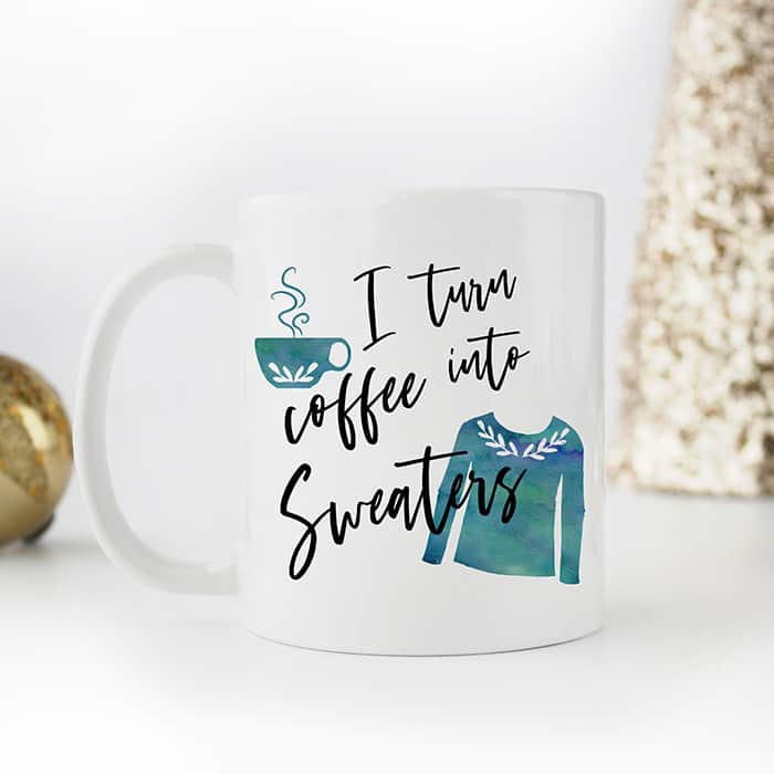 A white mug that reads, I turn coffee into sweaters with a teal sweater and cup of coffee pictured