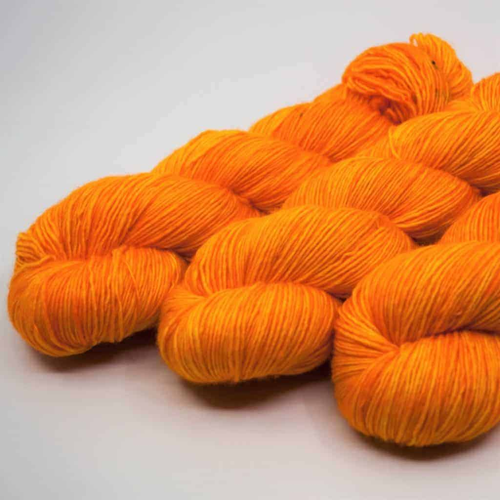 Three skeins of orange yarn