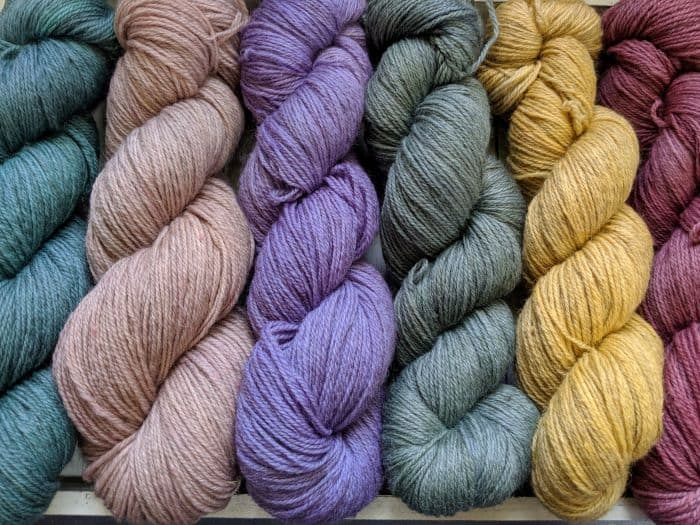 Skeins of tan, blue, green and yellow yarn