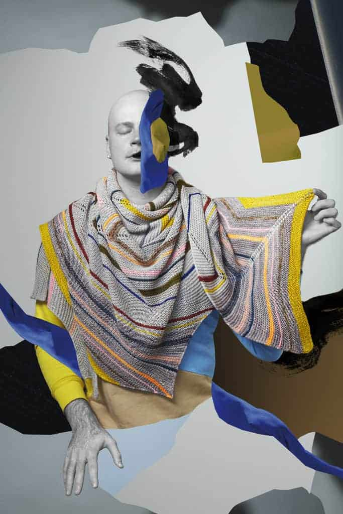 Stephen West models a multicolor striped shawl