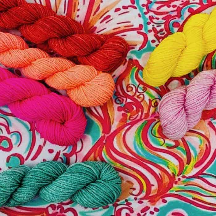 Skeins of teal, hot pink, orange, red, bright yellow and light pink yarn