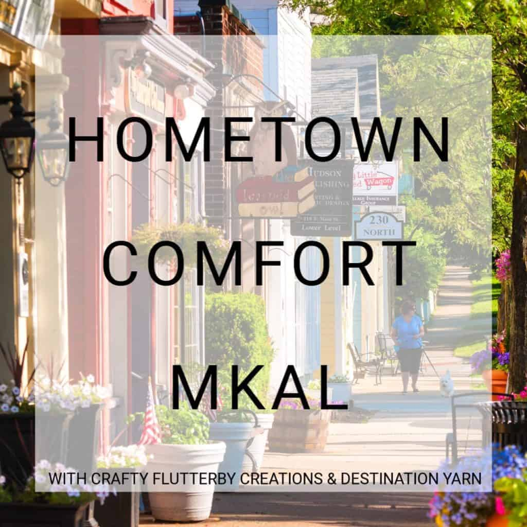 A picture of a downtown street and the words Hometown Comfort MKAL with Crafty Flutterby Creations and Destination Yarn