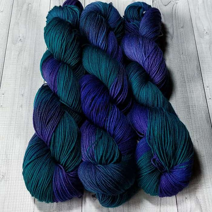 Three skeins of dark green and blue variegated yarn