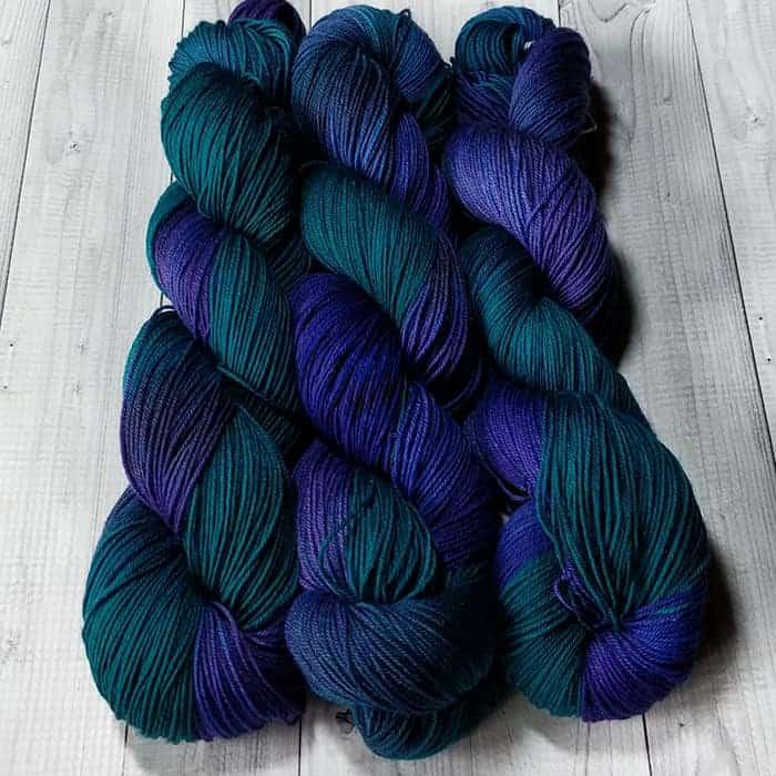 Three skeins of dark green and blue variegated yarn