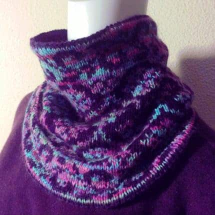 A colorwork cowl made with purple, pink and aqua yarn.
