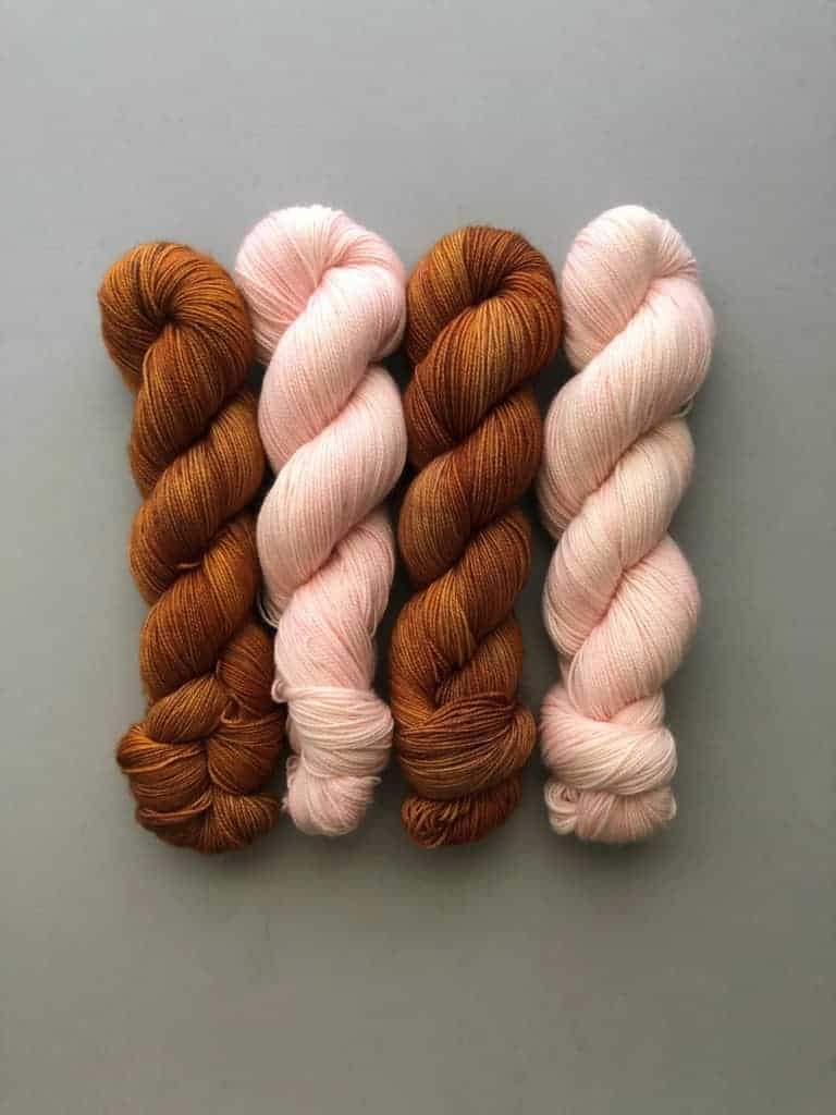 Skeins of golden brown and pale pink yarn.