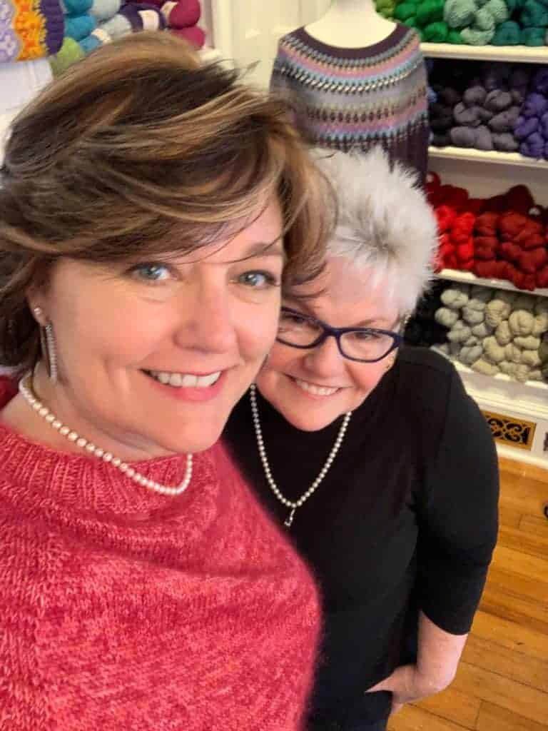 A woman with light brown hair, pearls and a pink sweater takes a selfie with a woman with gray hair and a black shirt.