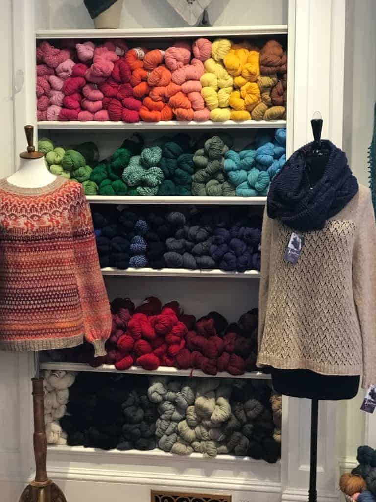 A link and taupe sweater in front of shelves stocked with a rainbow of yarn.