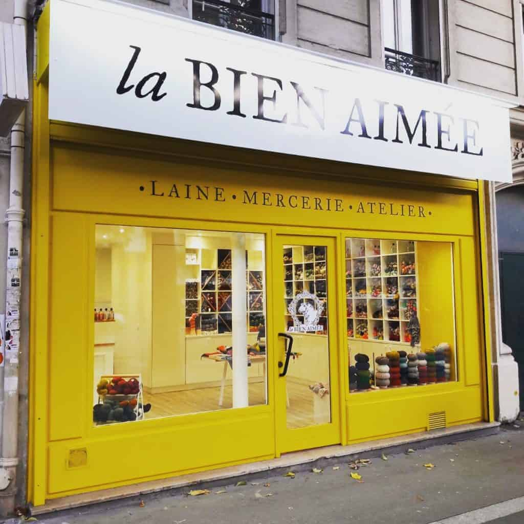 The yellow storefront of La Bien Aimée yarn.