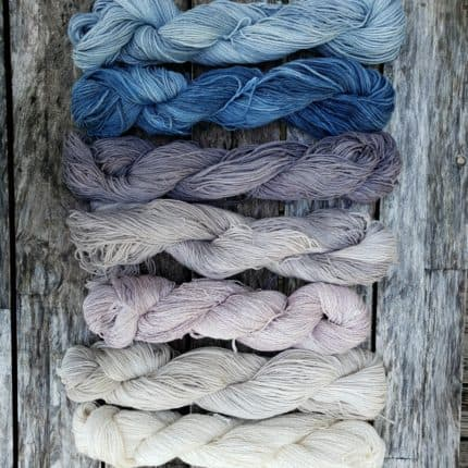 An ombre of 7 hanks of blue yarn on a piece of weathered wood.