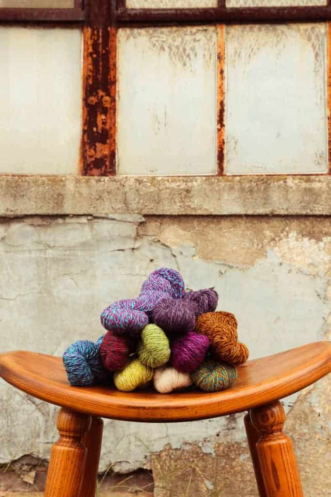 Skeins of colorful yarn on a curved wooden stool.