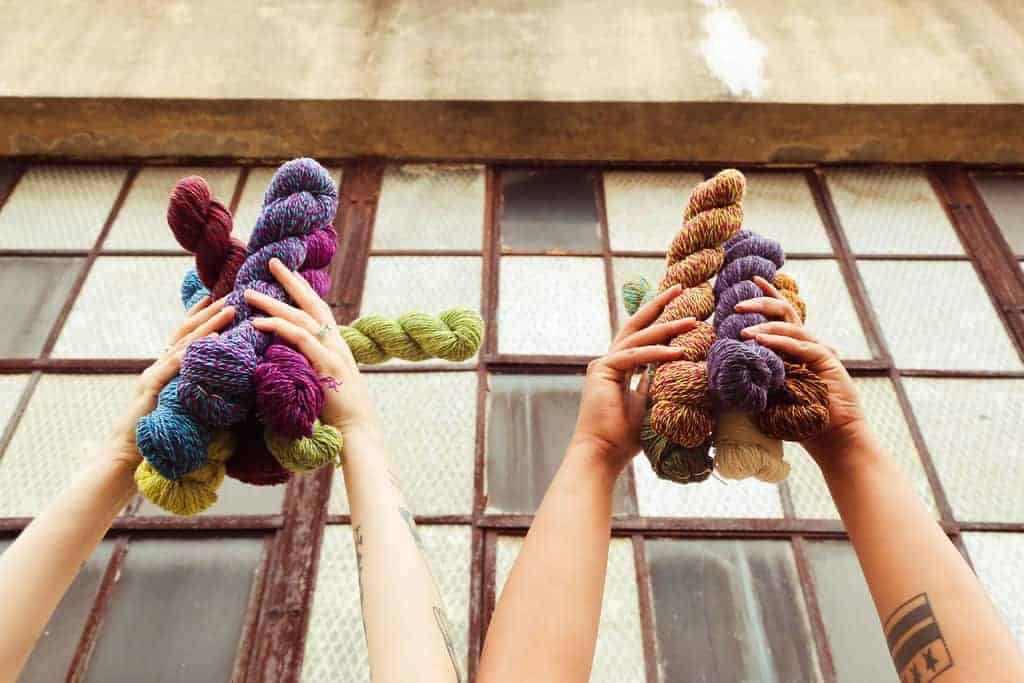Arms up in the air holding bundles of colorful yarn.