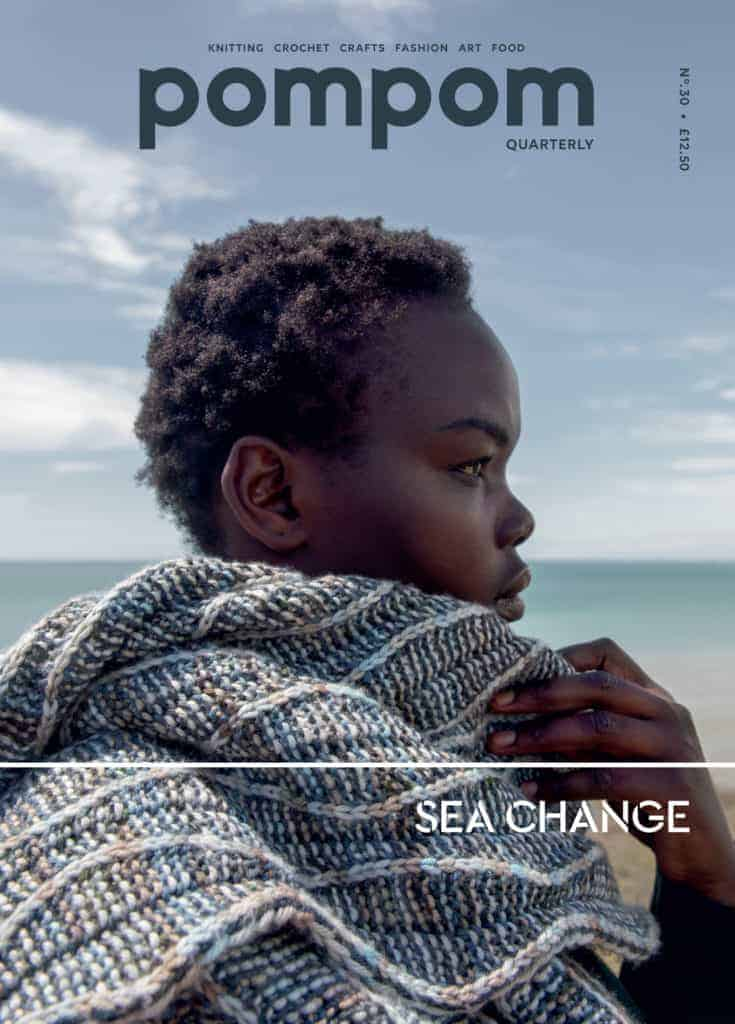 An African American woman models a blue and sand textured wrap on the cover of Pom Pom Quarterly