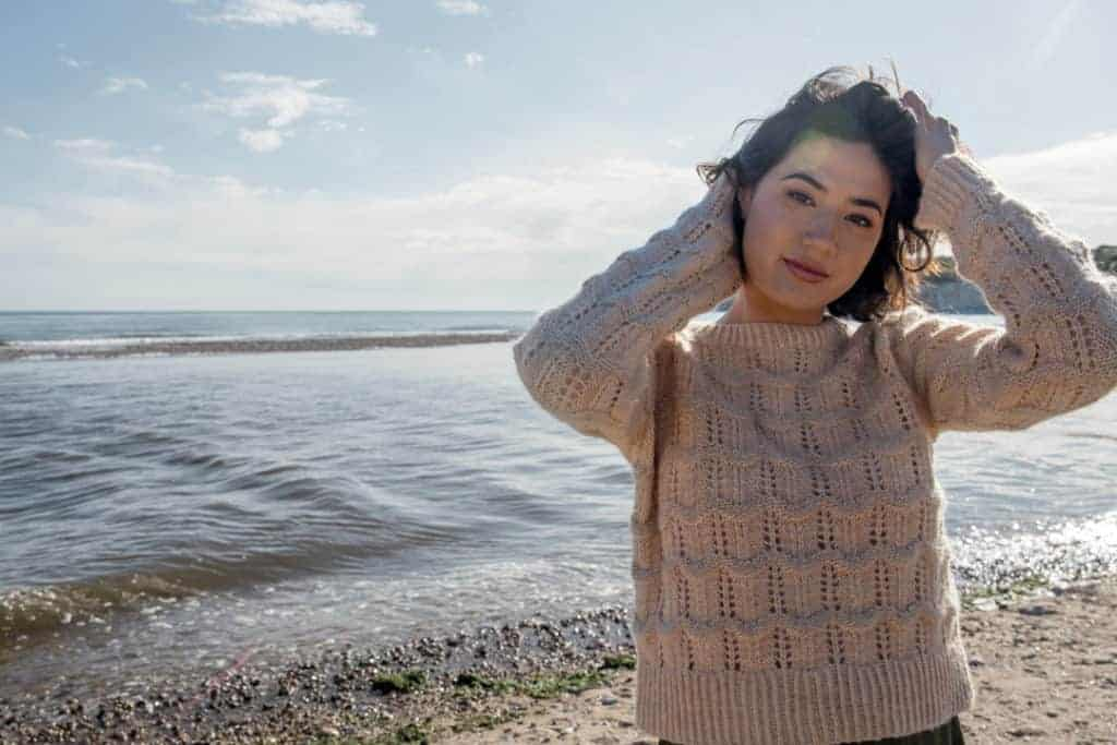 A sand colored cabled sweater modeled by the sea