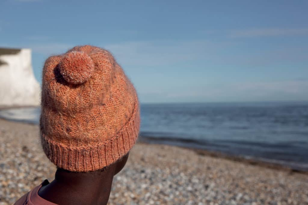 A peach hat with cables