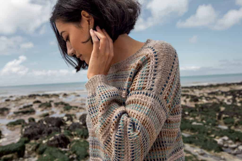 A woman models a mosaic sand and blue sweater