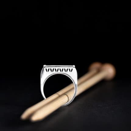 A silver stockinette stitch motif ring with a pair of wooden knitting needles.