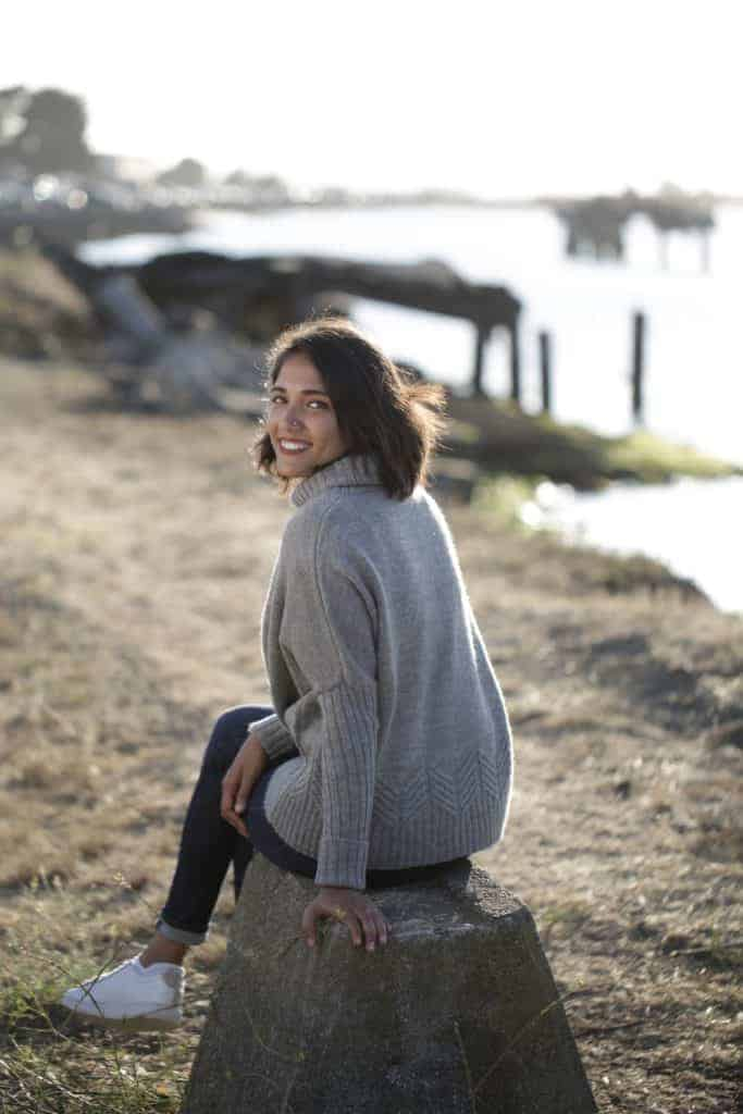 Woman models a gray sweater on a beach.
