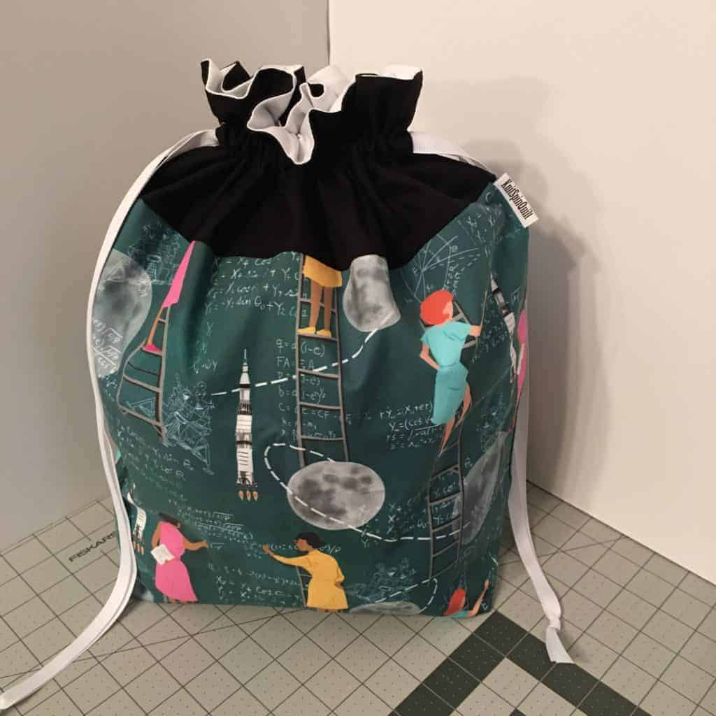 A drawstring bag with women scientist fabric.