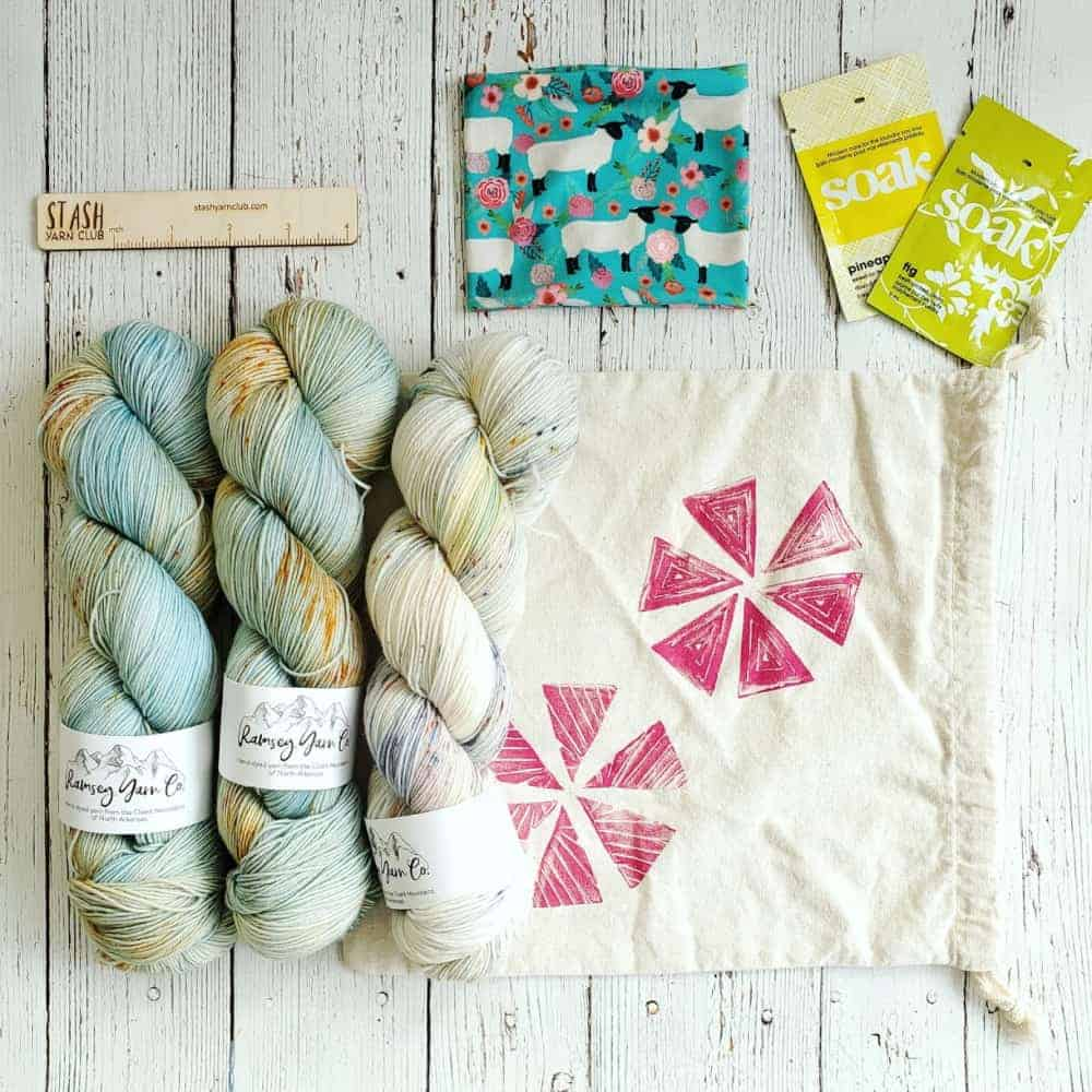 A kit with blue and gold yarn, a bag stamped with pink flowers and Soak wash.