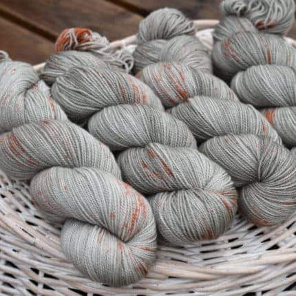 Silver yarn with orange speckles.