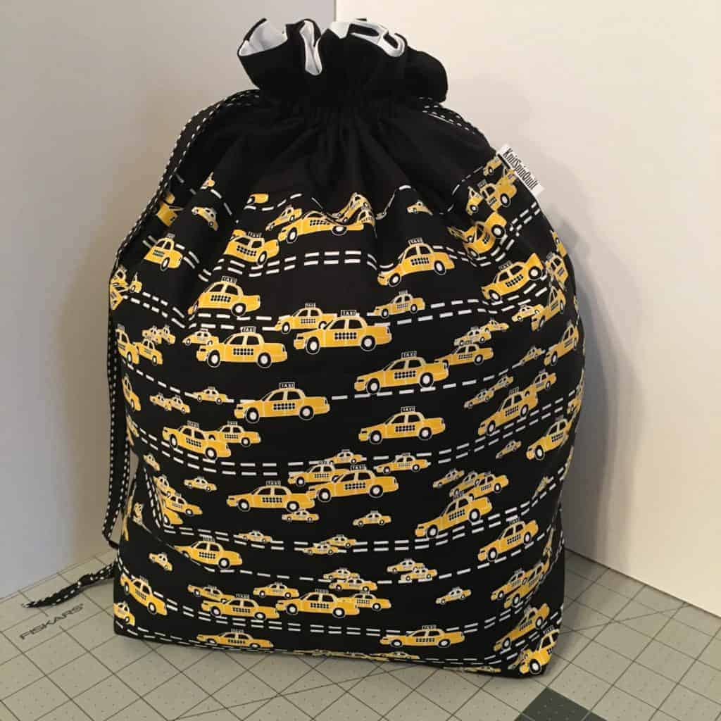 A black drawstring bag with yellow cabs.