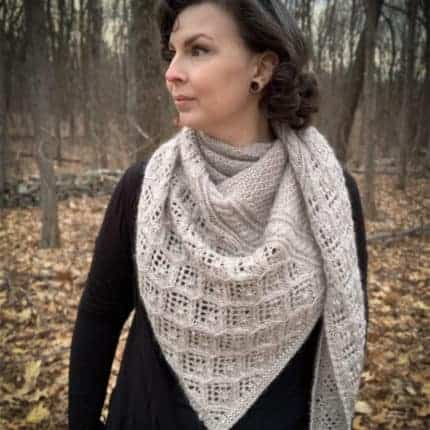 A woman models a thick, white, lacy shawl.