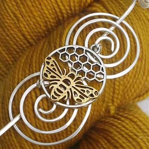 A bee and honeycomb on a silver shawl pin.