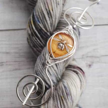 A dragonfly in amber in a silver shawl pin on a skein of gray yarn.