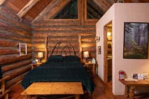 A green bed in a log cabin.