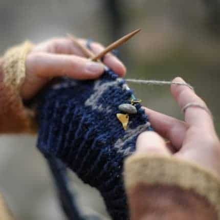 White hands hold blue and gray colorwork knitting.