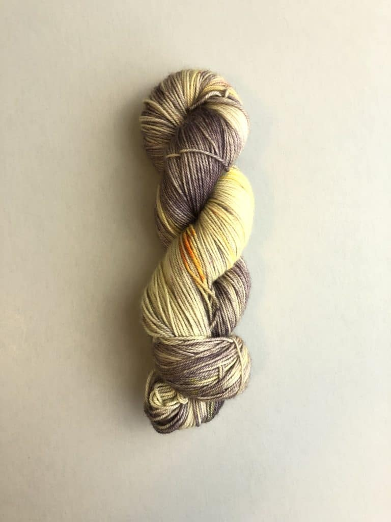 A skein of gray and amber yarn.