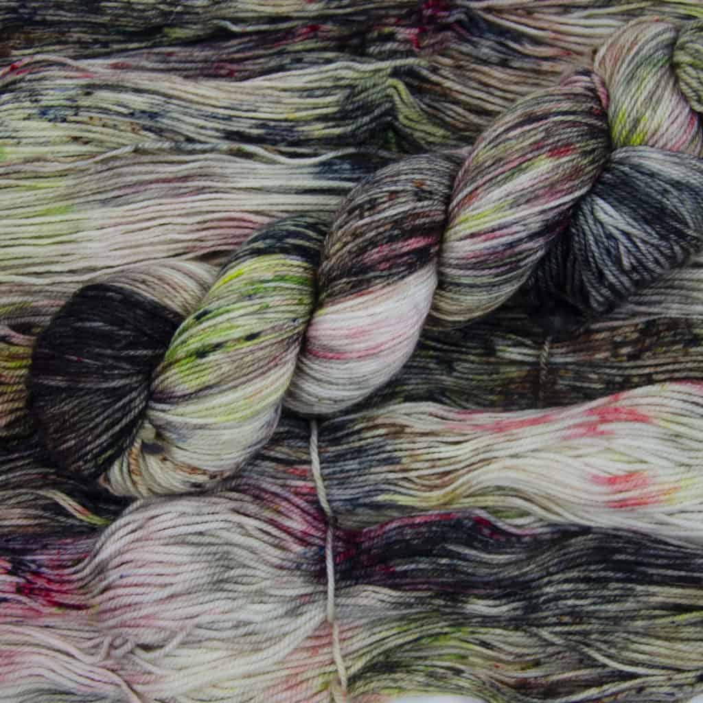 A skein of grey, green and red yarn.