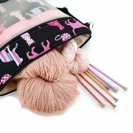 A pink and black bag with pink yarn and knitting needles.