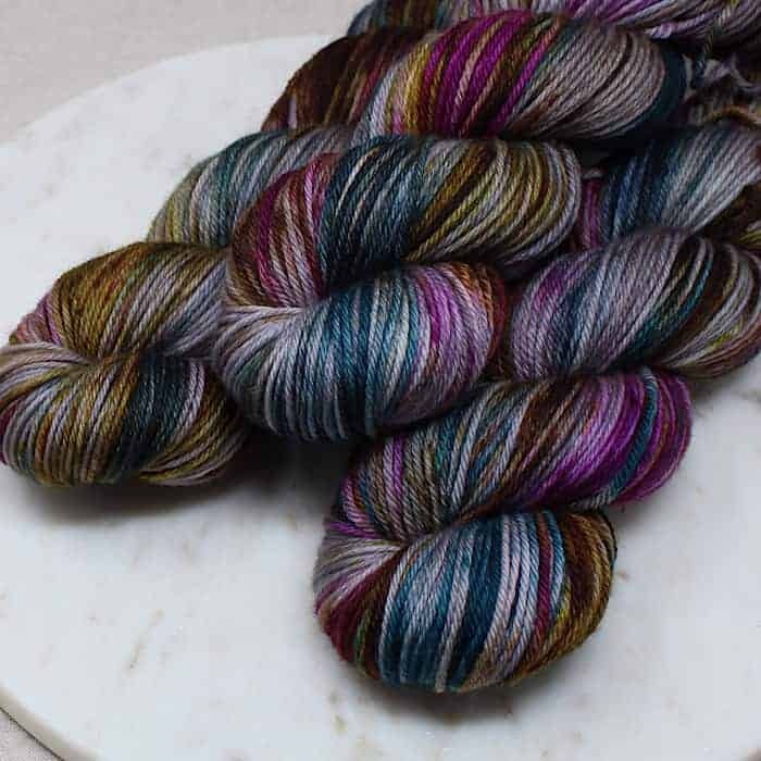 Gray yarn with pink, teal and yellow speckles.