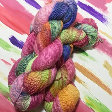 Skeins of pink, purple, green and orange yarn in front of a painting with the same colors.