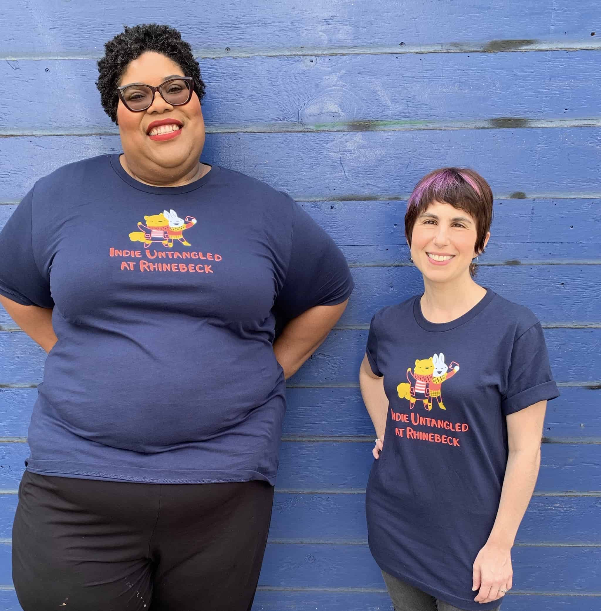 An African American, plus-sized woman with curly hair and a petite Caucasian woman with a pixie cut model matching navy T-shirts.