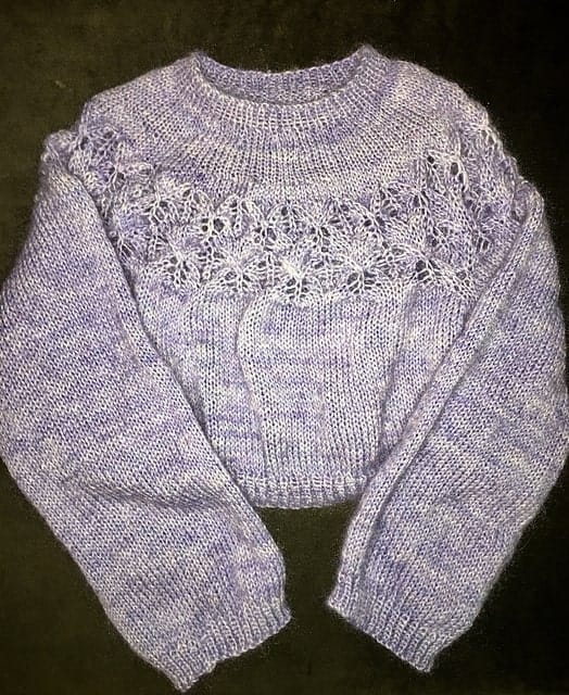A lilac sweater with a lacy yoke.