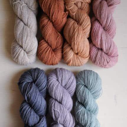 Skeins of soft orange, pink and blue yarn.