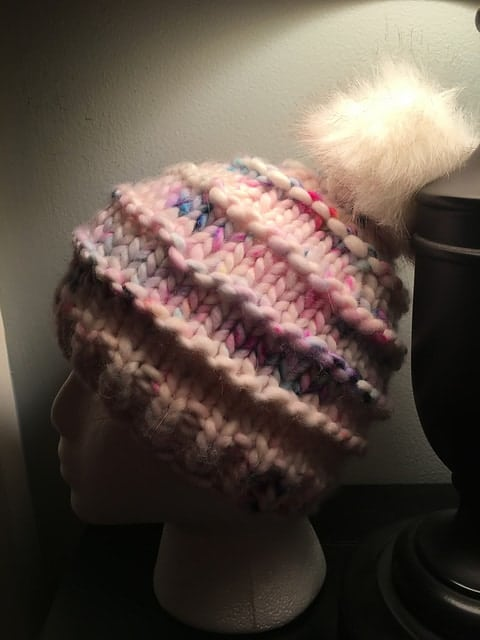 A pink hat with garter ridges and a white fur pompom.