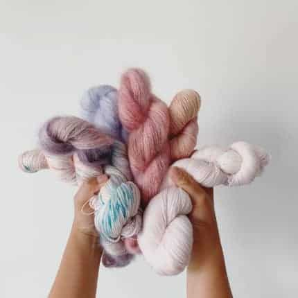 Hands hold up pastel skeins of yarn.