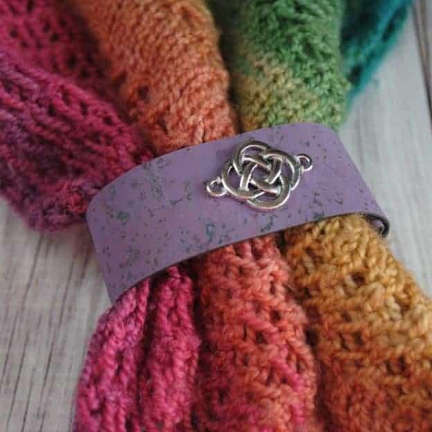 A purple shawl cuff with a silver Celtic knot.